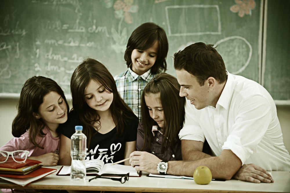 Cheerful kids at school room having education activity